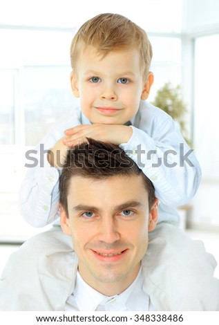 portrait of the father  holding his son on his shoulders. both look at the camera and smiling - stock photo