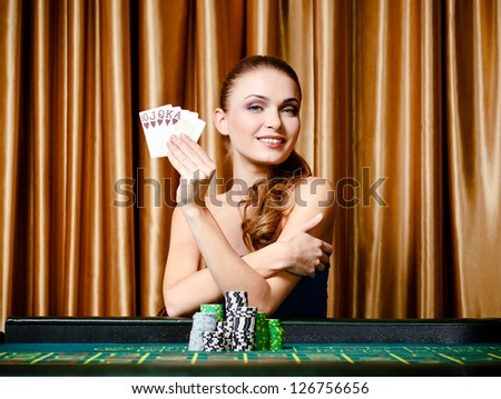 Portrait of the female gambler at the poker table with cards - stock photo