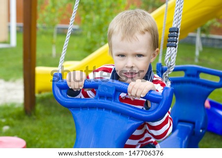 portrait of the four-year-old kid on a swing - stock photo