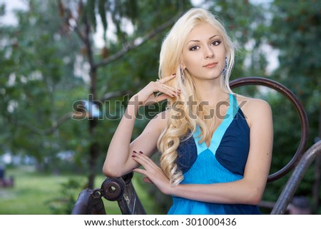 Portrait of the girl in blue dress sitting on the metallic armchair in the park                             - stock photo