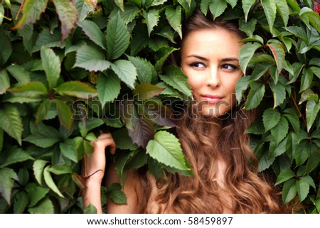 Portrait of the girl in green foliage - stock photo