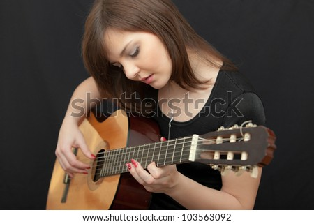 portrait of the girl playing on a guitar