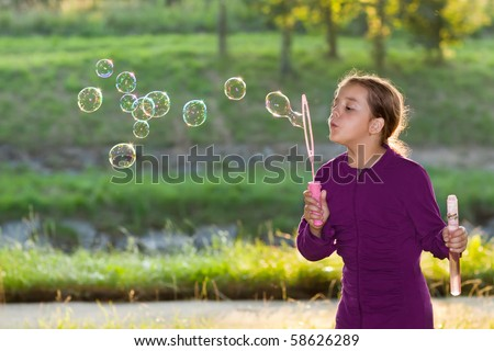 Portrait of the girl puts the bubbles in the park