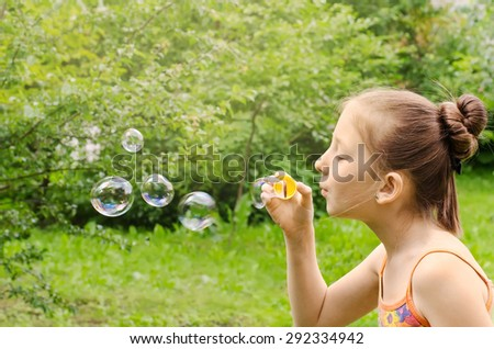 Portrait of the girl who are starting up soap bubbles - stock photo