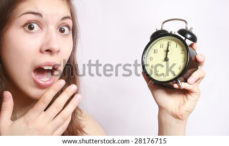 Portrait of the girl, with a fright looking at an alarm clock.