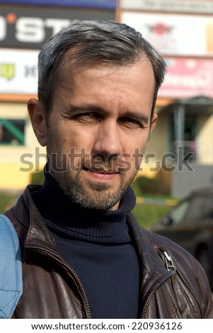 portrait of the gray haired unshaven man in a leather jacket - stock photo