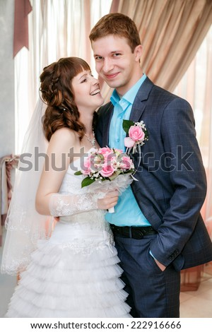 Portrait of the groom and the bride near a window - stock photo