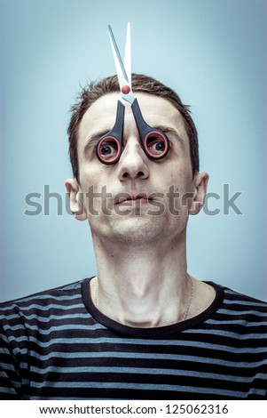 Portrait of the guy with scissors-mask on his face. - stock photo