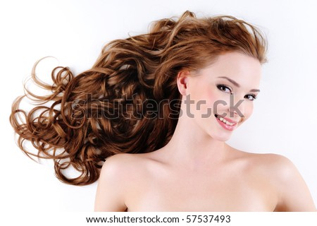 Portrait of the happy beautiful  woman with brown long ringlets hair - stock photo