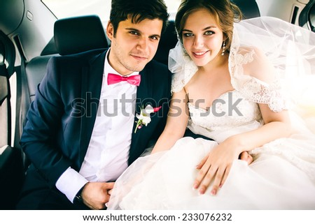 portrait of the happy bride and groom in the car - stock photo