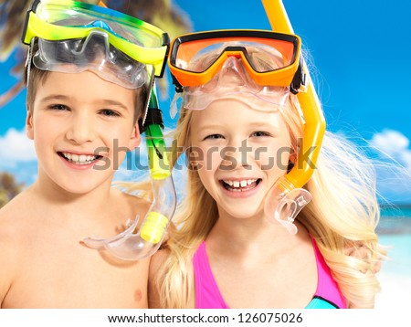 Portrait of the happy children enjoying at beach.  Brother and sister standing together in swimwear with swimming mask on head . - stock photo