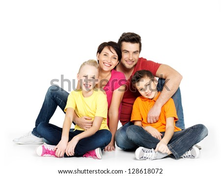 Portrait of the happy  family with two children sitting at studio on white floor - stock photo