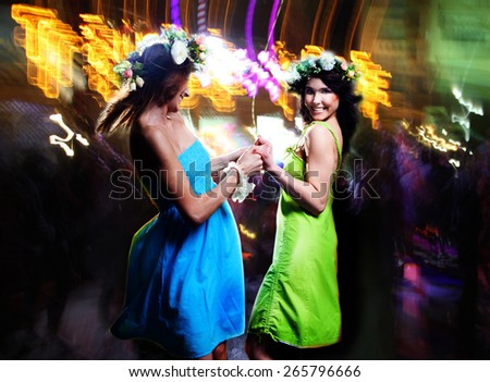 Portrait of the happy girlfriends dancing in a disco.  - stock photo