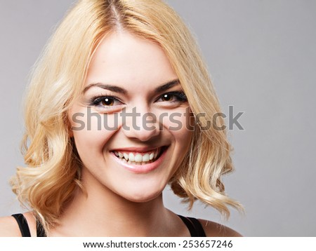 Portrait of the happy smiling young lady posing in studio grey background.