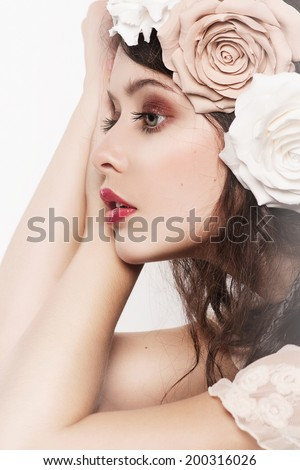 Portrait of the innocent girl bride with big beautiful eyes,  gentle make-up and hairstyle isolated on white background. Trendy fashion wedding look. Big  Flowers and bridal hairdo - stock photo