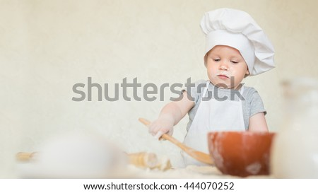 Portrait of the little boy in a suit of the cook sculpts dough. Baby make dinner in chef suit. Cooking concept with free text space - copy space - stock photo