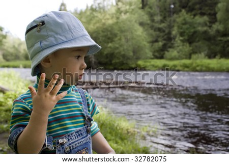 Portrait of the little boy of summer wood and  river backgrounds - stock photo