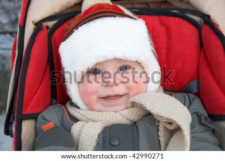 Portrait of the little boy on walk in a carriage in the winter - stock photo