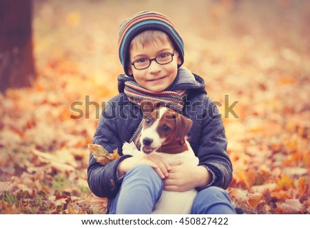 portrait of the little boy playing with his cute pet in the park - stock photo