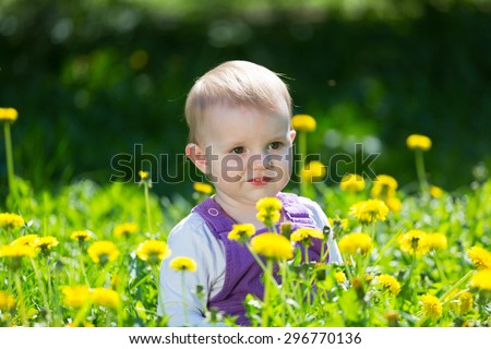 Portrait of the little girl among the blossoming dandelions - stock photo