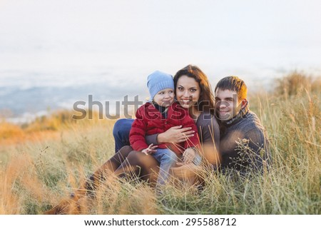 Portrait of the little girl with a funny hat and father and mother smiling outdoors. Family leisure outdoors concept