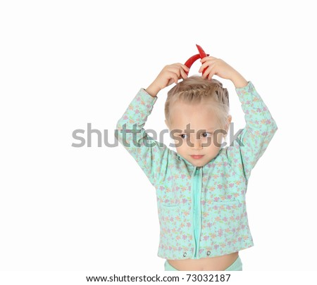 Portrait of the little girl with horns of red chili peppers - stock photo