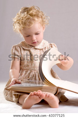 Portrait of the little girl with the book - stock photo