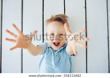 portrait of the little smiling boy lying on the floor with arms outstretched - stock photo
