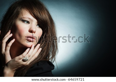Portrait of the magnificent young woman on a dark background - stock photo