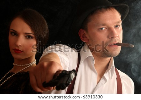 Portrait of the man in a hat with a cigar and a pistol and the beautiful woman. In style of a retro. - stock photo