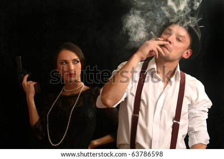 Portrait of the man in a hat with a pistol and the beautiful woman. In style of a retro. - stock photo