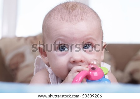 Portrait of the newborn child with a toy in a hand