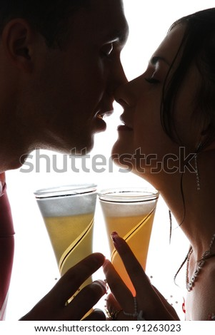 portrait of the newlyweds on studio shooting with glasses of champagne - stock photo