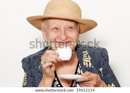 Portrait of the old woman with a coffee cup on a light background - stock photo