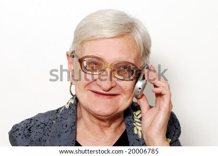 Portrait of the old woman with a mobile phone on a light background - stock photo