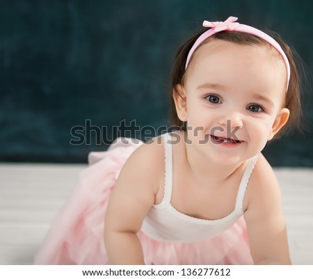 Portrait of the one year old baby wearing ballet suit indoor - stock photo