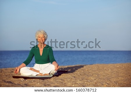 Portrait of the senior woman meditating on the seashore with lots of copyspace. Elder woman doing relaxation exercise on sandy beach during morning. - stock photo