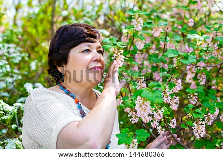 Portrait of the senior woman smelling spring blossom - stock photo