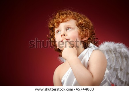 Portrait of the small thoughtful boy with wings behind the back on a red background - stock photo
