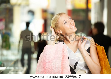 Portrait of the smiling blonde in shop with bags - stock photo