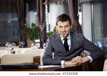 Portrait of the smiling business man at restaurant - stock photo