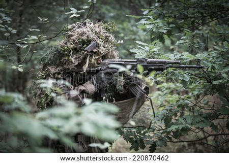 portrait of the soldier dressed in ghille suit, aiming with  assault rifle in forest. rifle painted camouflage.  - stock photo