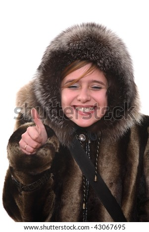 Portrait of the teenager in a fur coat and a cap showing a good sign - stock photo