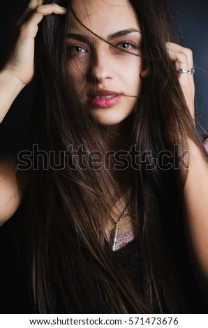 Portrait of the upper half of tender young woman with swarthy skin, flying long dark hair, opened beautiful eyes and full lips. Studio. Low Key. Fashion. Beauty. Advertising.