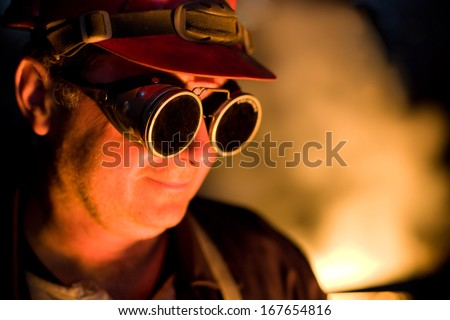 Portrait of the worker with protective goggles looking down, red color is a reflection of the molten metal. Very high heat and purple fringing. The inscription on the glasses is not a trademark. - stock photo