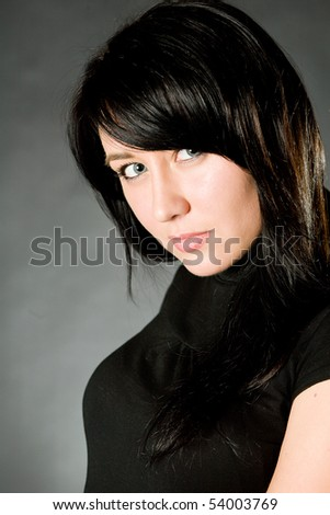 Portrait of the young beautiful brunette on a grey background