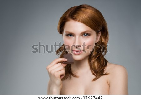 Portrait of the young beautiful  girl with a piece of chocolate - stock photo