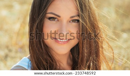 Portrait of the young beautiful smiling woman outdoors enjoying summer sun. wind in hair.