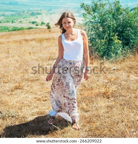 Portrait of the young beautiful smiling woman outdoors enjoying summer sun. wind in hair. girl in a long skirt and with long hair poses in warm spring day. Photo with instagram style filters - stock photo