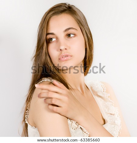 Portrait of the young long-haired girl in an elegant dress on a gray background - stock photo